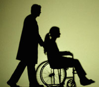 Silhouette of a woman being pushed in a wheelchair by a health aide.