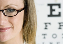 Woman wearing glasses standing in front of an eye chart