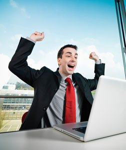 Man sitting in front of laptop, smiling and raising his arms.