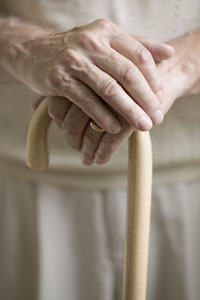 Hands clasped over a walking cane.