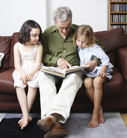 Grandfather sitting and reading to his two granddaughters